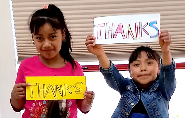 """2 girls with """"Thanks"""" signs"""