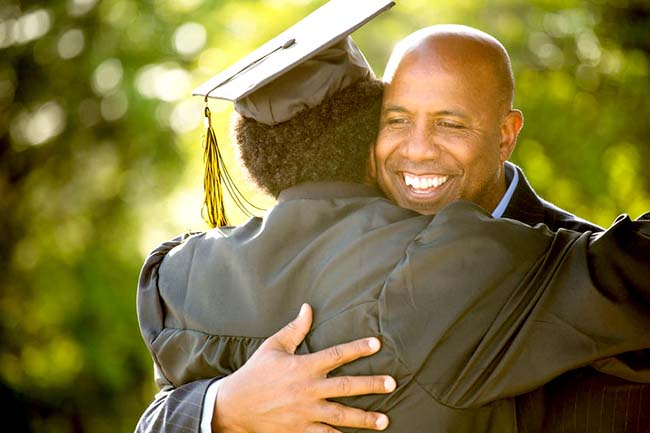 Young man graduate hugging proud father