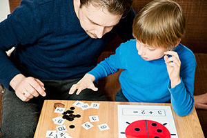 Father coaching young child with math